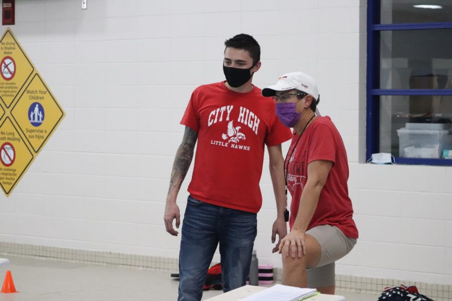 Assistant coach Ike Casey (left) and head coach Mandi Kowal (right) watch the technique of their swimmers at a practice during the first week of the season.