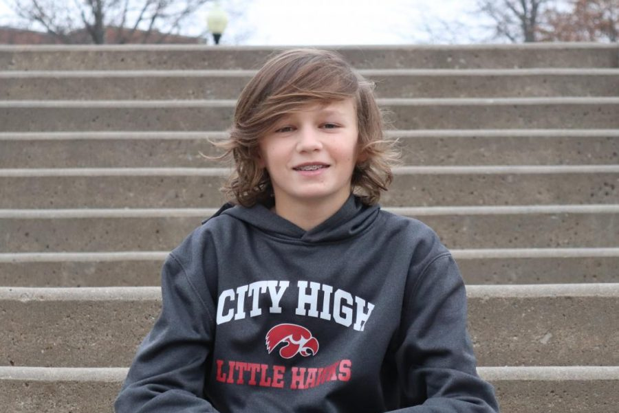 Arthur Hall 24 poses for a picture on the front steps of City High. As a freshman, he is already one of the best players on the City High boys golf team.