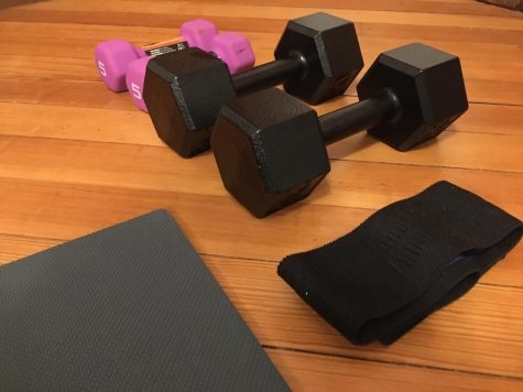Four weights, a resistance band, and an exercise mat lying on the ground. These are all equipment that can be used for exercise during quarantine