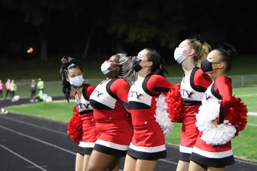 The City High cheer team pumps up the student section during football's season opener. On August 28, City defeated Davenport Central 35-14.