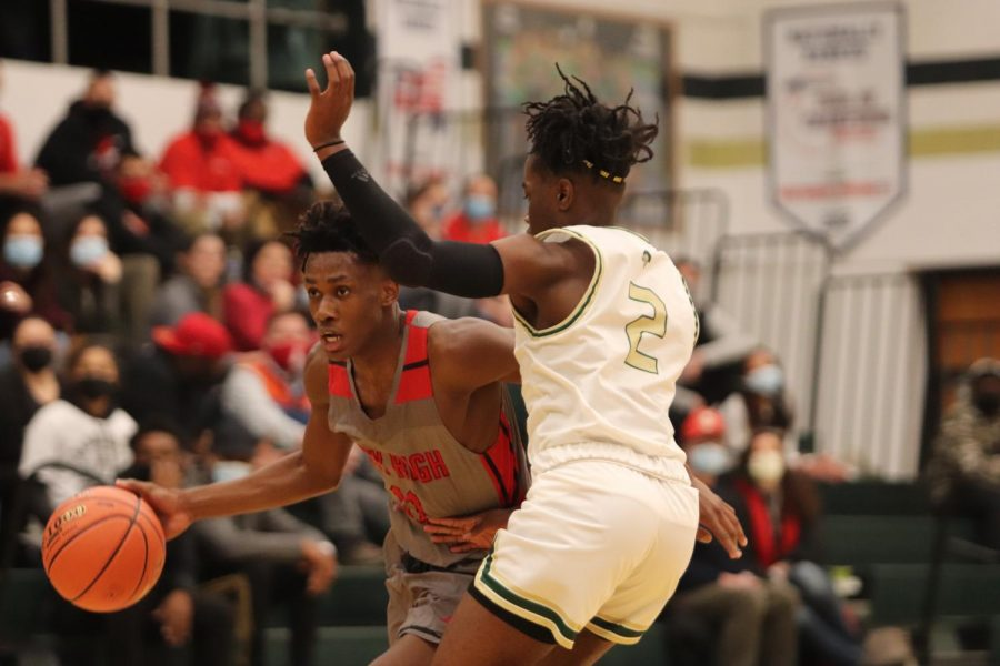 Byron Benton '21 dribbles around a West High defender during basketball's 77-71 overtime win.