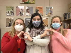 Mrs. Johannesen, Mrs. Basile, and Mrs. Staak make hearts with their hands.