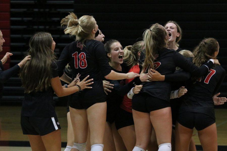 The varsity volleyball team celebrates their win against Linn-Mar.