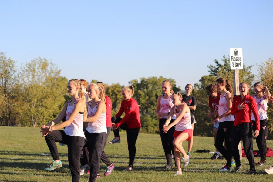 A group of the 10 Varsity runners warm up before racing with smiles on their faces.