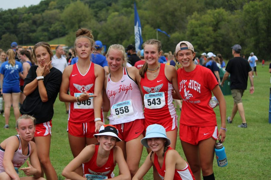 A group of JV and Varsity girls pose for a photo after finishing their race in the Luther All-American meet in Decorah, Iowa .