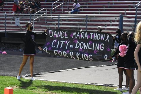 City High Cheerleaders displaying the Dance Marathon banner at the City vs. Dowling football game.